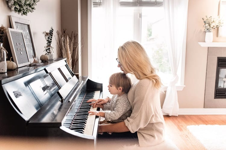 Mother Teaching Child How To Play Piano