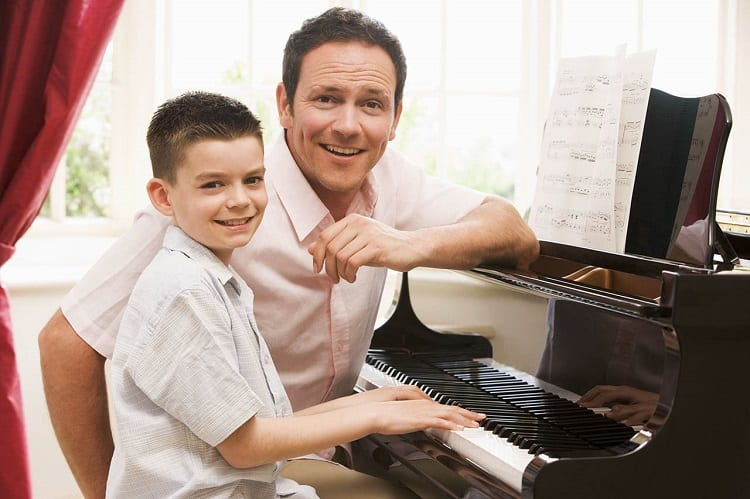 Man Giving Young Boy Piano Lessons