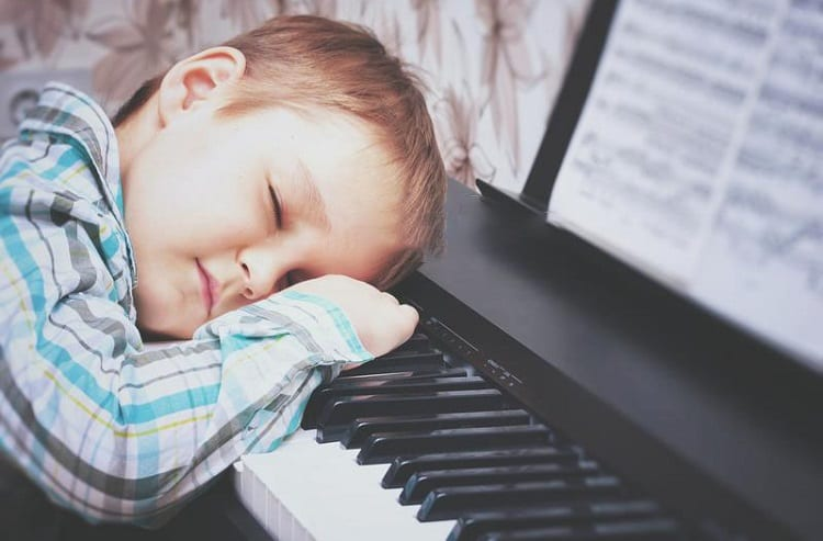 Young Boy Sleeping On Piano Keys